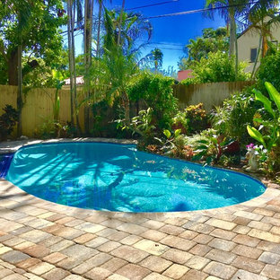 Large backyard brick and kidney-shaped lap pool photo in Miami