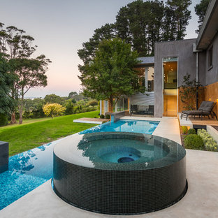 Inspiration for a large contemporary backyard custom-shaped infinity pool in Melbourne with a hot tub and concrete slab.