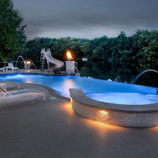 Foto de piscinas y jacuzzis infinitos, actuales, extra grandes, a medida, en patio trasero, con adoquines de piedra natural