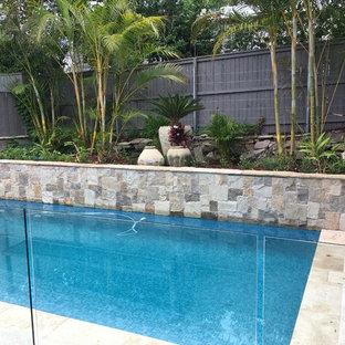 Imagen de piscina minimalista en patio trasero