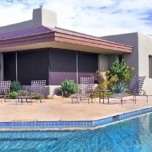 Diseño de piscina tradicional renovada, de tamaño medio, en forma de L y interior, con losas de hormigón