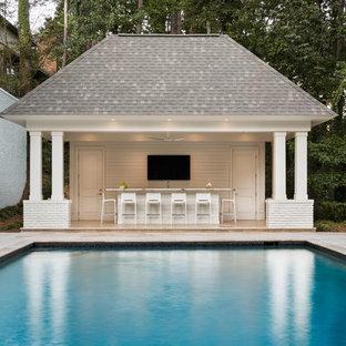 Idéer för att renovera en stor funkis rektangulär pool på baksidan av huset, med poolhus och naturstensplattor