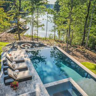 Photo of a large rustic back rectangular infinity swimming pool in Charlotte with a hot tub and natural stone paving.