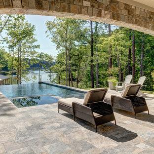 На фото: большие прямоугольные бассейны-инфинити на заднем дворе в стиле рустика с джакузи и покрытием из каменной брусчатки