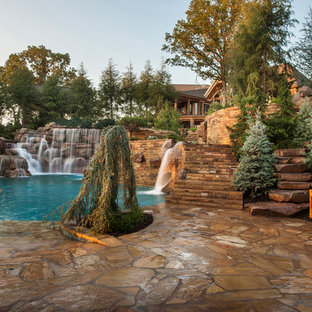 Example of a huge mountain style backyard stone and custom-shaped natural water slide design in Oklahoma City