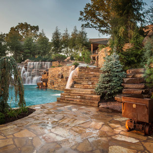 Design ideas for an expansive country backyard custom-shaped natural pool in Oklahoma City with a water feature and natural stone pavers.