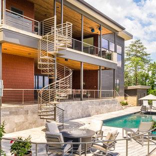 Ejemplo de piscina alargada, contemporánea, rectangular, en patio trasero, con suelo de baldosas