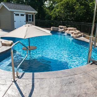 Ejemplo de piscina con fuente natural, romántica, de tamaño medio, a medida, en patio trasero, con suelo de hormigón estampado