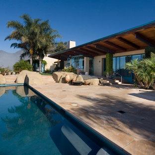 Ejemplo de piscina con fuente de estilo americano, grande, en patio trasero, con adoquines de piedra natural
