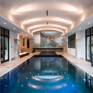 Foto de casa de la piscina y piscina tradicional renovada, extra grande, interior y rectangular, con adoquines de piedra natural