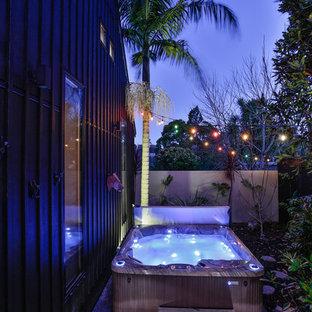 Idee per una piccola piscina fuori terra industriale rettangolare in cortile con una vasca idromassaggio e pedane