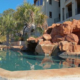 Foto di una grande piscina naturale tropicale personalizzata dietro casa con un acquascivolo e lastre di cemento