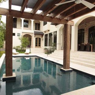ヒューストンの大きい長方形トランジショナルスタイルのおしゃれなプール (天然石敷き) の写真