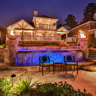 Inspiration for an expansive eclectic backyard custom-shaped infinity pool in Houston with a water feature and tile.