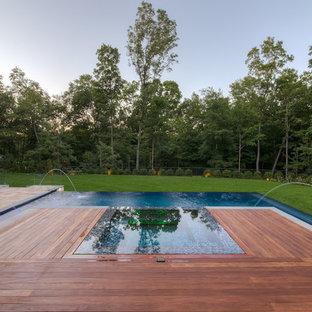 Diseño de piscinas y jacuzzis infinitos, grandes, rectangulares, en patio trasero, con adoquines de piedra natural