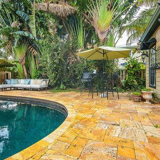 Ejemplo de piscina alargada, bohemia, de tamaño medio, tipo riñón, en patio trasero