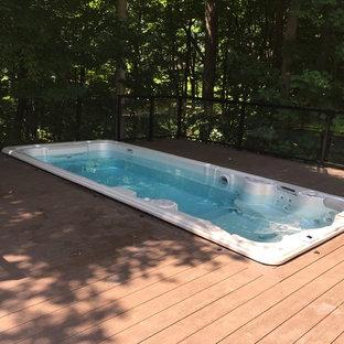 Cette photo montre une piscine sur une terrasse en bois chic avec un bain bouillonnant.