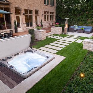 Immagine di una piscina minimalista dietro casa con una vasca idromassaggio e pedane