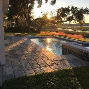 Foto de piscinas y jacuzzis alargados, tradicionales renovados, de tamaño medio, rectangulares, en patio trasero, con suelo de hormigón estampado