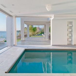 Diseño de piscina alargada, tradicional renovada, grande, interior y rectangular, con losas de hormigón