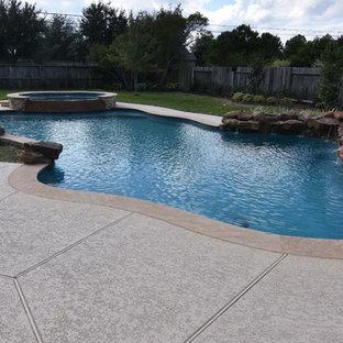ヒューストンの広いオーダーメイドトロピカルスタイルのおしゃれな自然ろ過プール (デッキ材舗装) の写真
