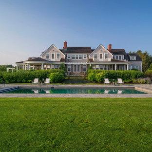 Imagen de casa de la piscina y piscina alargada, costera, extra grande, rectangular, en patio trasero, con adoquines de piedra natural
