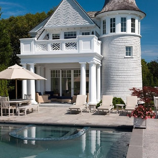 This is an example of a traditional rectangular pool in Boston with decomposed granite and a pool house.