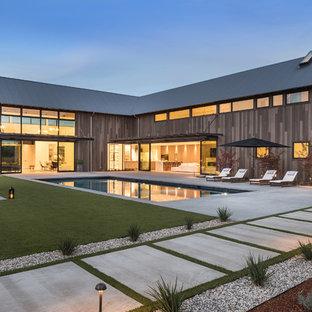 Foto de piscina alargada, campestre, extra grande, rectangular, en patio trasero, con losas de hormigón
