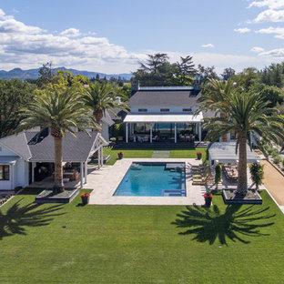 Ejemplo de casa de la piscina y piscina alargada, campestre, de tamaño medio, rectangular, en patio trasero, con adoquines de piedra natural