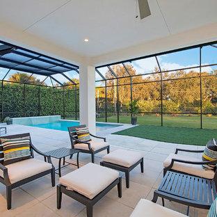 Idee per una grande piscina monocorsia tropicale rettangolare dietro casa con pavimentazioni in cemento e fontane