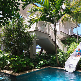 Esempio di un'ampia piscina a sfioro infinito tropicale personalizzata dietro casa con un acquascivolo e pavimentazioni in pietra naturale