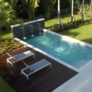 Imagen de piscina con fuente alargada, moderna, extra grande, en forma de L, en patio, con adoquines de hormigón
