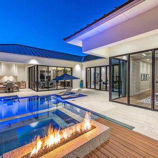 Imagen de piscina contemporánea, grande, a medida, en patio trasero, con suelo de baldosas