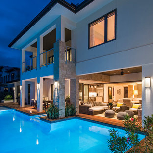 Immagine di una piscina moderna rettangolare di medie dimensioni e dietro casa con una vasca idromassaggio e pedane
