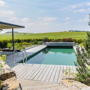 Foto de piscina alargada, de estilo de casa de campo, de tamaño medio, rectangular, en patio trasero, con entablado