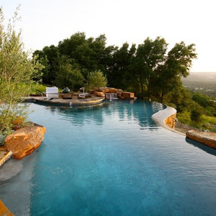 Example of a large classic backyard stone and custom-shaped infinity pool fountain design in Austin