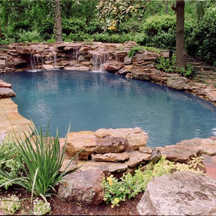 Photo of a mid-sized eclectic backyard custom-shaped natural pool in Houston with a water feature and natural stone pavers.