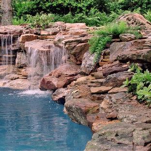 Diseño de piscina con fuente natural, bohemia, de tamaño medio, a medida, en patio trasero, con adoquines de piedra natural