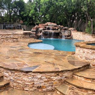 Foto de piscina natural, rústica, grande, tipo riñón, en patio trasero, con privacidad y adoquines de piedra natural