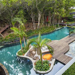 Inspiration for a tropical backyard custom-shaped infinity pool in Other with decking.