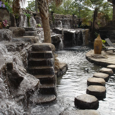 Example of a large mountain style backyard stone and custom-shaped natural pool fountain design in Seattle