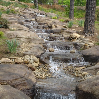 Inspiration for a huge rustic backyard stone and custom-shaped natural pool fountain remodel in Seattle
