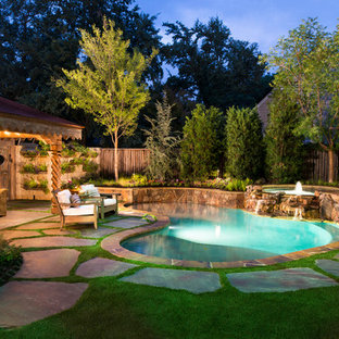 Photo of a large eclectic backyard custom-shaped natural pool in Dallas with a hot tub and natural stone pavers.