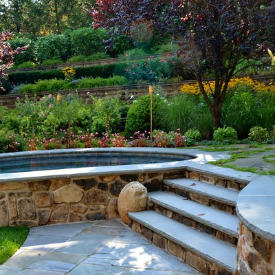 Hot tub - mid-sized rustic backyard stone and kidney-shaped natural hot tub idea in Newark