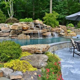 Diseño de piscina natural, rústica, grande, tipo riñón, en patio trasero, con adoquines de piedra natural