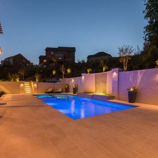 Foto de piscina con tobogán actual, de tamaño medio, a medida, en patio trasero, con adoquines de piedra natural