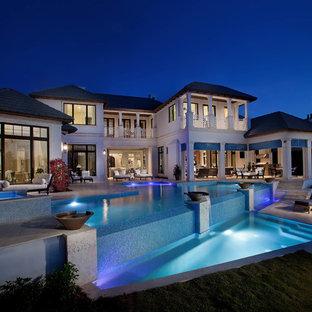 Large tropical backyard custom-shaped infinity pool in Miami.