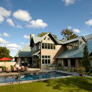 Ejemplo de piscina con fuente alargada, de estilo americano, grande, rectangular, en patio trasero, con adoquines de piedra natural