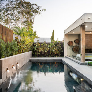 Inspiration for a mid-sized contemporary backyard rectangular pool in Melbourne with a water feature and concrete slab.