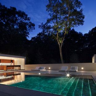 Ejemplo de casa de la piscina y piscina infinita, moderna, grande, rectangular, en patio trasero, con losas de hormigón